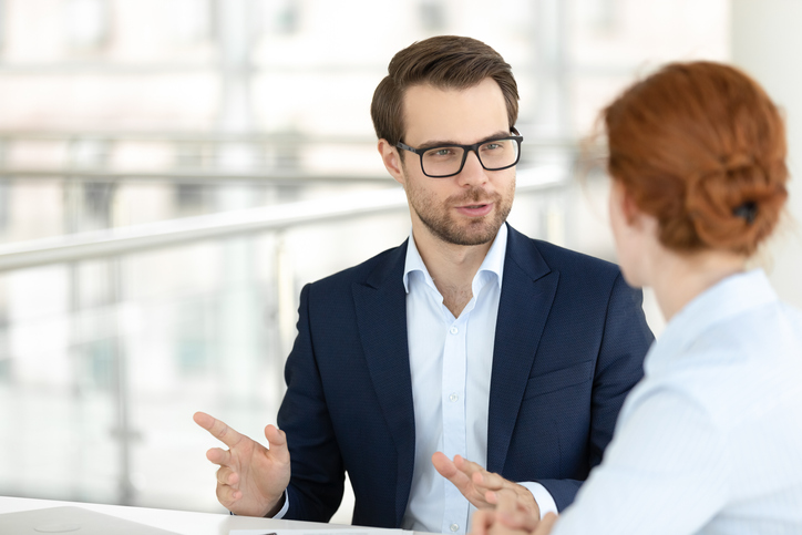 Handsome smiling male office worker talking with female colleague
